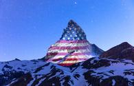 Matterhorn mountain illuminated with the American flag.