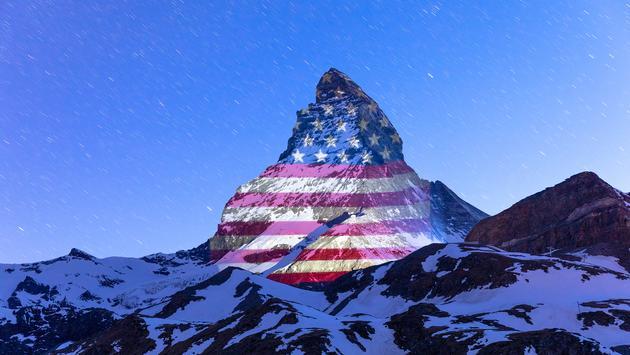 Matterhorn mountain illuminated with the American flag.