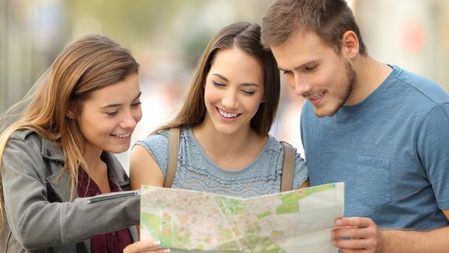 Three tourists consulting a paper map