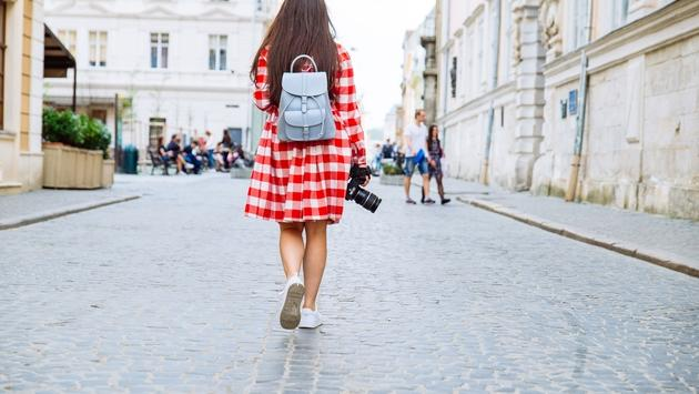 woman walking by city with camera in her hand