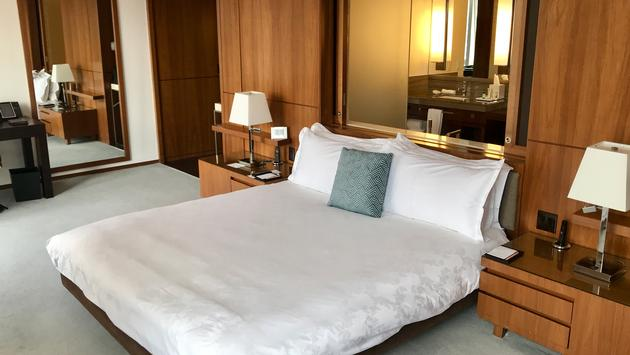 Hotel room with plush bed and walnut cabinetry