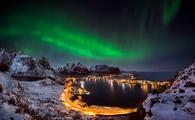 The northern lights shine over Reine, Norway.