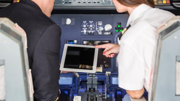 pilots checking flight information on digital tablet