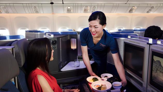 Flight attendant serving a meal in United Polaris business class
