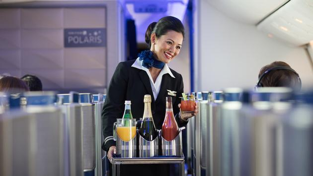 Flight attendant serving drinks in United Polaris business class