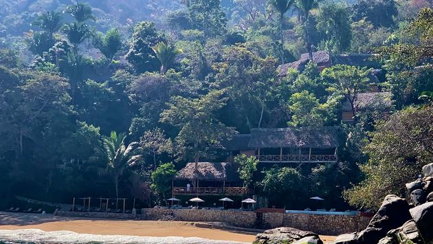 Eco resort on hillside with beach and ocean in foreground