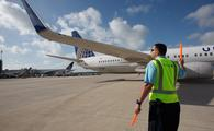 United ramp serviceman marshalls in a plane at Houston Bush Intercontinental Airport