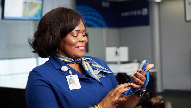 United Airport Customer Service Representative using an iPhone