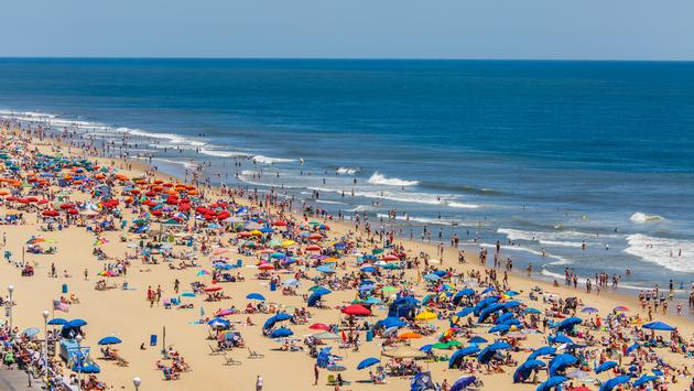 A crowded U.S. beach filled with people and umbrellas.
