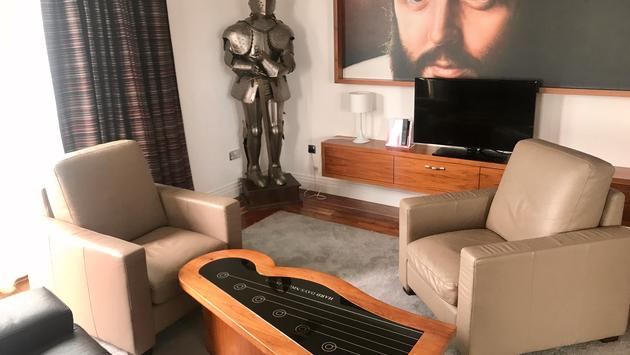 The Paul McCartney Suite with a knight's armor, guitar coffee table and painting of Sir Paul McCartney