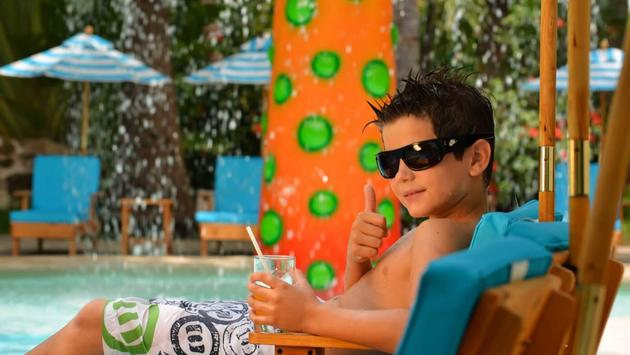 Youngster relaxing in a kid-sized pool lounger at Hotel Oasis Palm in Cancun, Mexico.