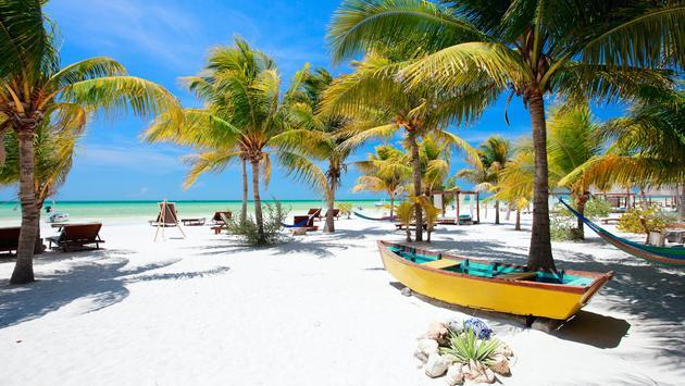 A beach with hammocks and palm trees in Isla Holbox, Mexico