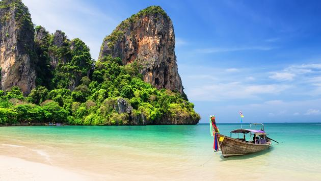 Traditional wooden longtail boat moored on a beach in Thailand.