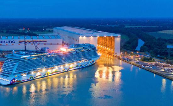 Norwegian Encore emerges from the Meyer Werft shipbuilding dock in Papenburg, Germany.