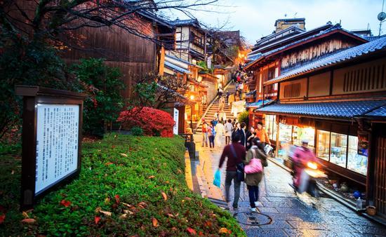Tourists walk on a street leading to Kiyomizu-dera Temple in Kyoto, Japan