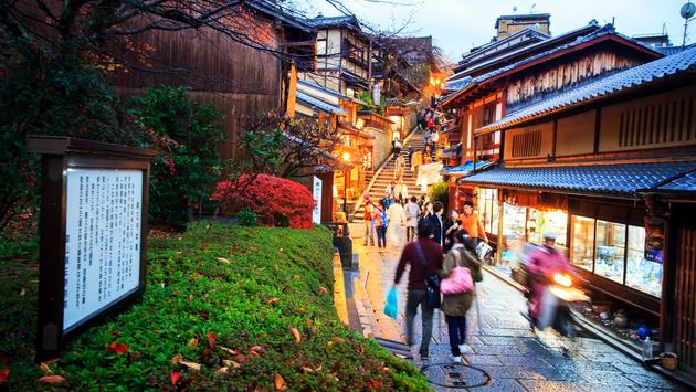 Tourists walk on a street leading to Kiyomizu-dera Temple in Kyoto, Japan