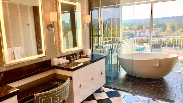 A luxurious bathroom with marble tile and a bathtub with a view