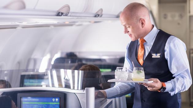 JetBlue flight attendant serving drinks in Mint section