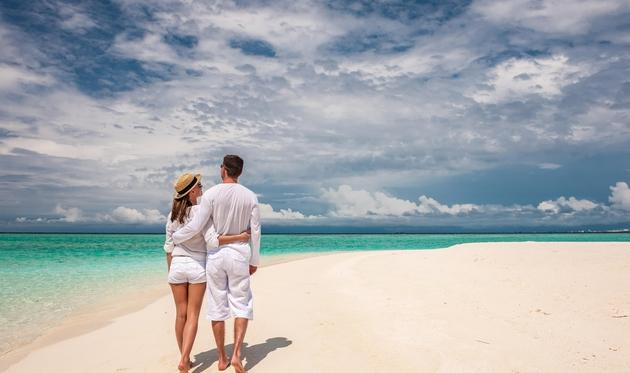 Couple walking on the beach in The Maldives