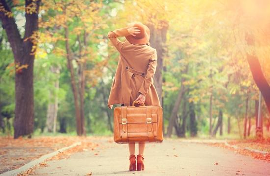 woman with luggage in park