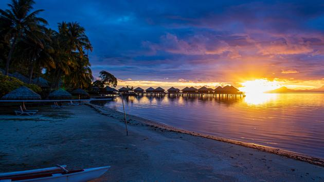 Sunset from beach with view of overwater bungalows