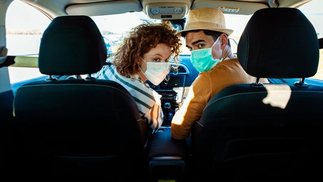 A couple wearing face masks on a road trip