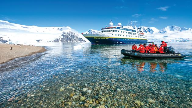A zodiac cruises in front of a Lindblad Expeditions vessel.
