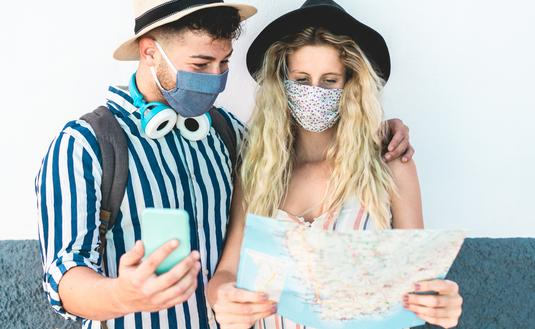 Young couple examining a map while vacationing amid COVID-19.