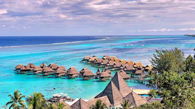 Overview of hotel with overwater bungalows on turquoise lagoon