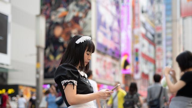 Cosplay housemaid watching smart phone.