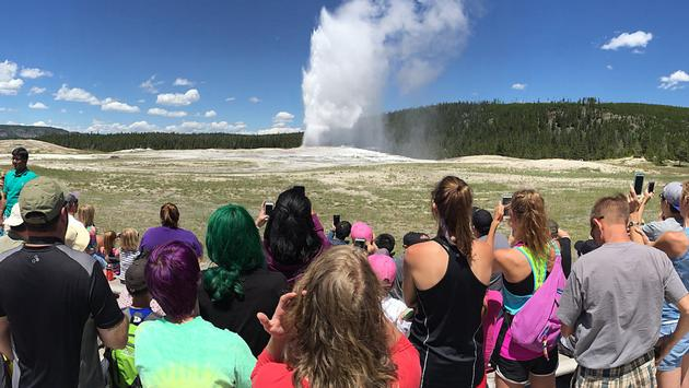 Crowd of visitors watching 'Old Faithful' geyser erupt in Yellowstone National Park, Wyoming.