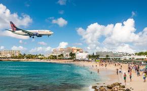 Delta flight approaches St Maarten's Princess Juliana Airport above onlookers on Maho Beach