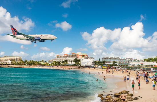 Delta flight approaches St Maarten's Princess Juliana Airport above onlookers on Maho Beach