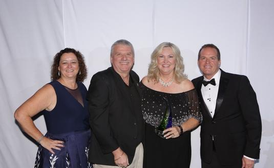 PHOTO: Debbie Fiorino, left, and Drew Daly, right, honor 2018 Dream Vacations Franchisee of the Year Susan Pretkus-Combs; also pictured is 2017 honoree Mike Ziegenbalg. (Photo by www.TheLXA.com courtesy of Dream Vacations/CruiseOne)