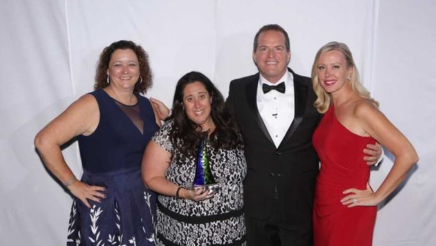 Debbie Fiorino, left, and Drew Daly honor 2018 Cruises Inc. Agent of the Year Melissa Cohn, with trophy. Also pictured at right is the 2017 honoree Lori Foster. (Photo by www.TheLXA.com courtesy of Dream Vacations/CruiseOne)