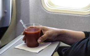 A glass of tomato juice on an airplane tray