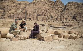 Travelers take a tea break with a local woman in Petra, Jordan