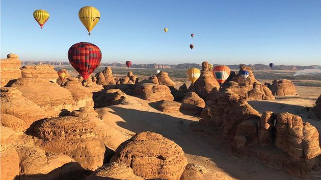 Hot air balloons floating above a Saudi Arabian landscape.