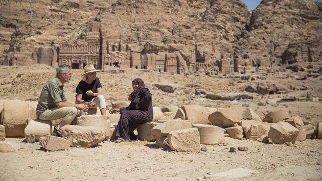 Travelers take a tea break with a local woman in Petra, Jordan