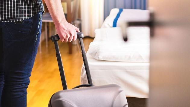 Man pulling suitcase and entering room (Photo via Tero Vesalainen / iStock / Getty Images Plus)
