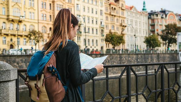Woman stands and looks at the map (Photo via franz12 / iStock / Getty Images Plus)