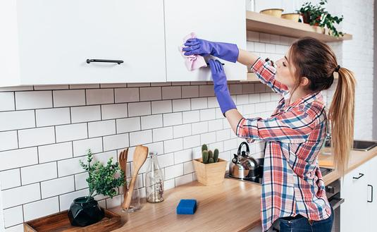 Woman in gloves cleaning cabinet (Photo via undrey / iStock / Getty Images Plus)