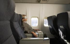 A woman using a sleeping mask on an airplane