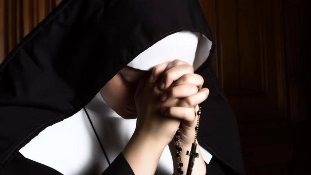 Nun folding hands holding a rosary praying