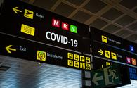 "Airport information panel emblazoned with ""Covid-19""."