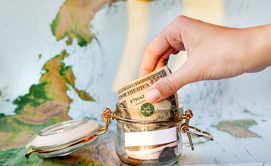 Collecting money for travel. Glass tin as moneybox with cash (Photo via Aksenovko / iStock / Getty Images Plus)