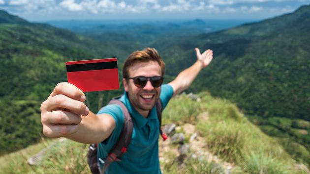 Man showing credit card while standing on top of mountain (Photo via Koldunova_Anna / iStock / Getty Images Plus)