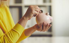 Woman inserts a coin into a piggy bank (Photo via Rostislav_Sedlacek / iStock / Getty Images Plus)