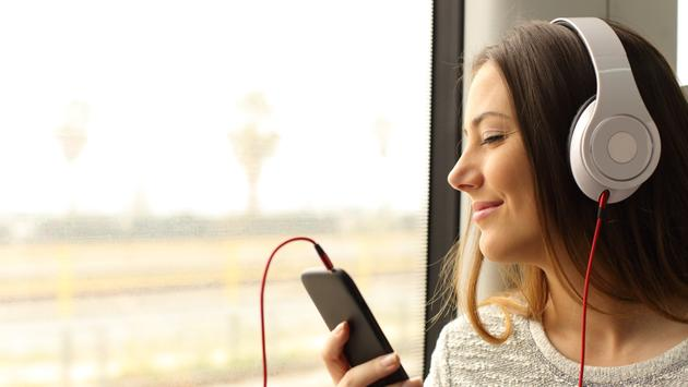 Woman listening to music with a smartphone and headphones while traveling by train.