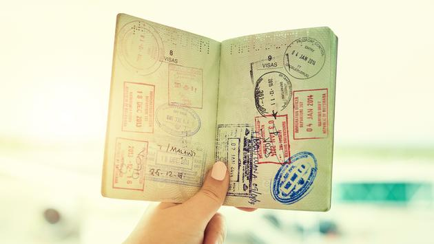 Person holding a passport filled with stamps.